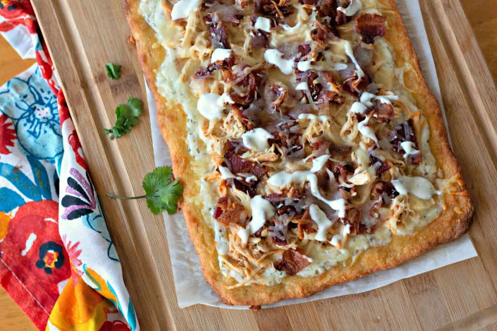 A pizza sitting on top of a wooden cutting board, with Bacon