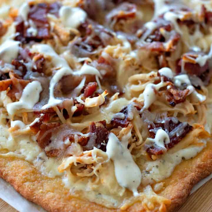 A pizza sitting on top of a wooden cutting board, with Bacon and Chicken