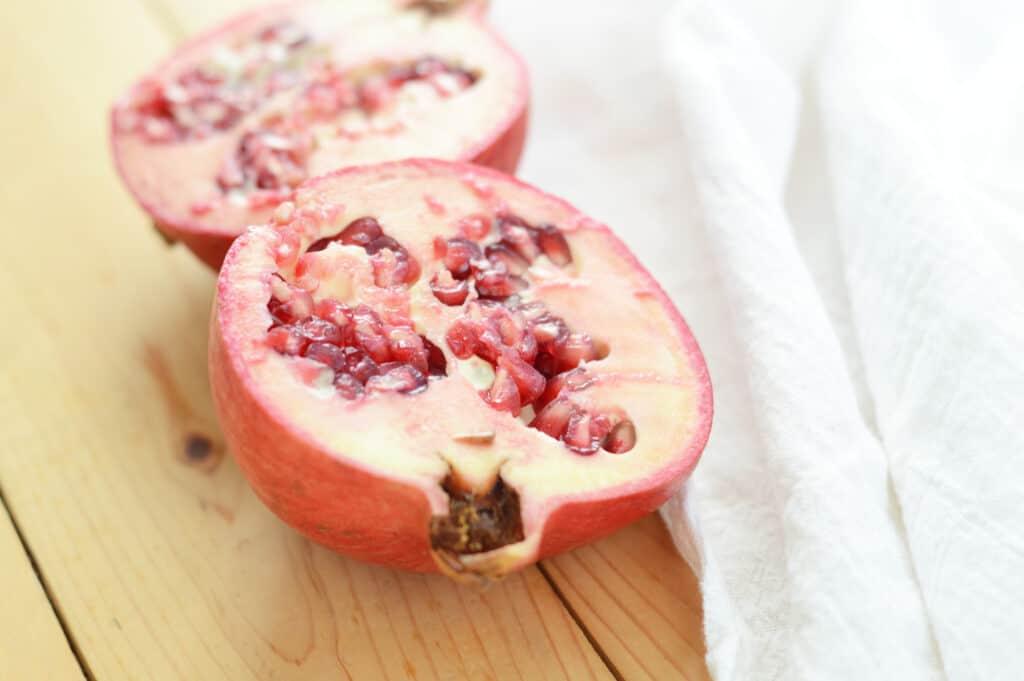 A pomegranate on a cutting board
