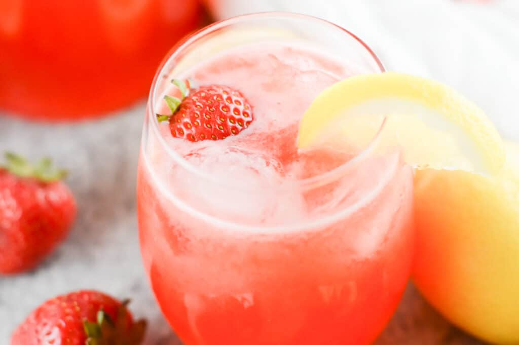 Horizontal shot of glass filled with strawberry lemonade, garnished with strawberries and lemon slice