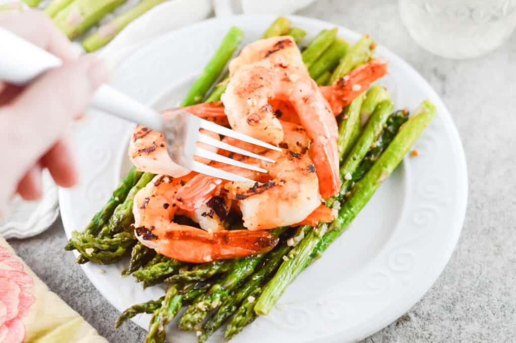Horizontal bird\'s-eye-view shot of fork picking up blackened shrimp over asparagus