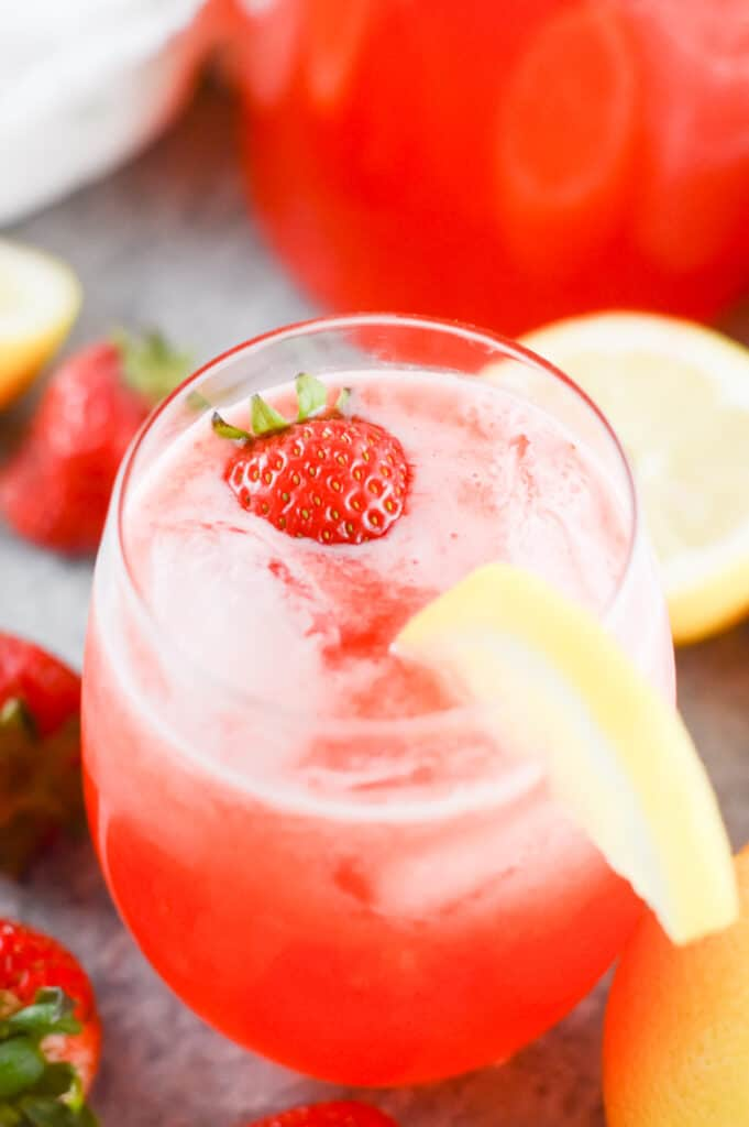 Vertical bird's-eye-view shot of glass filled with strawberry lemonade