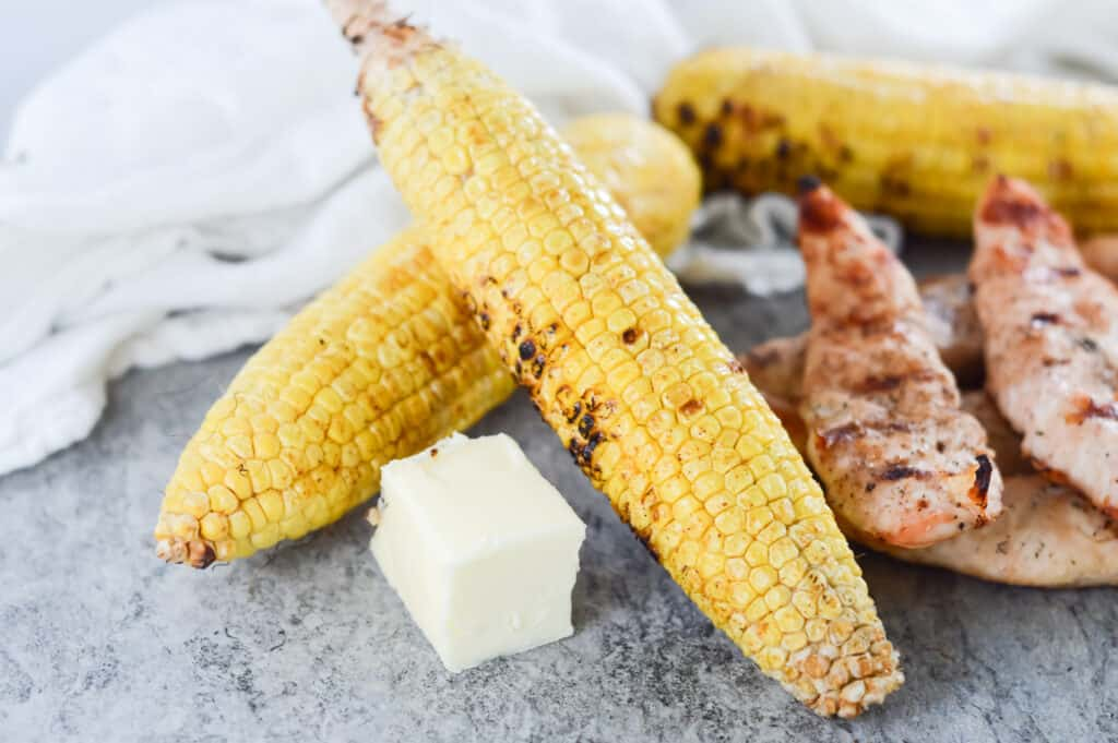 Horizontal shot of two pieces of corn on the cob and butter; chicken in the background