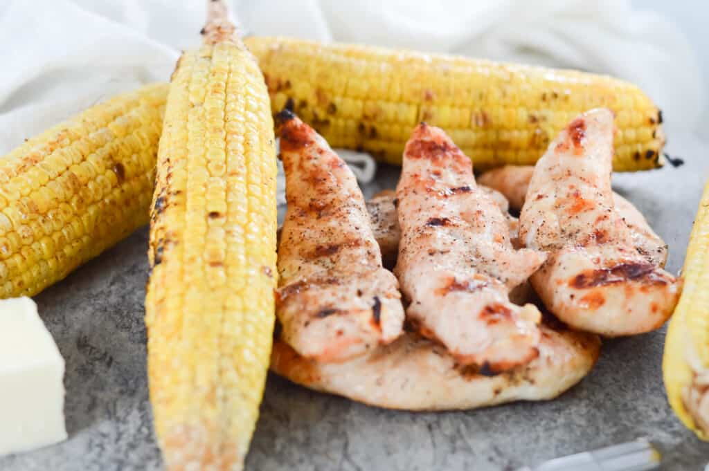 Horizontal shot of stacked pieces of grilled chicken and stacked pieces of corn on the cob