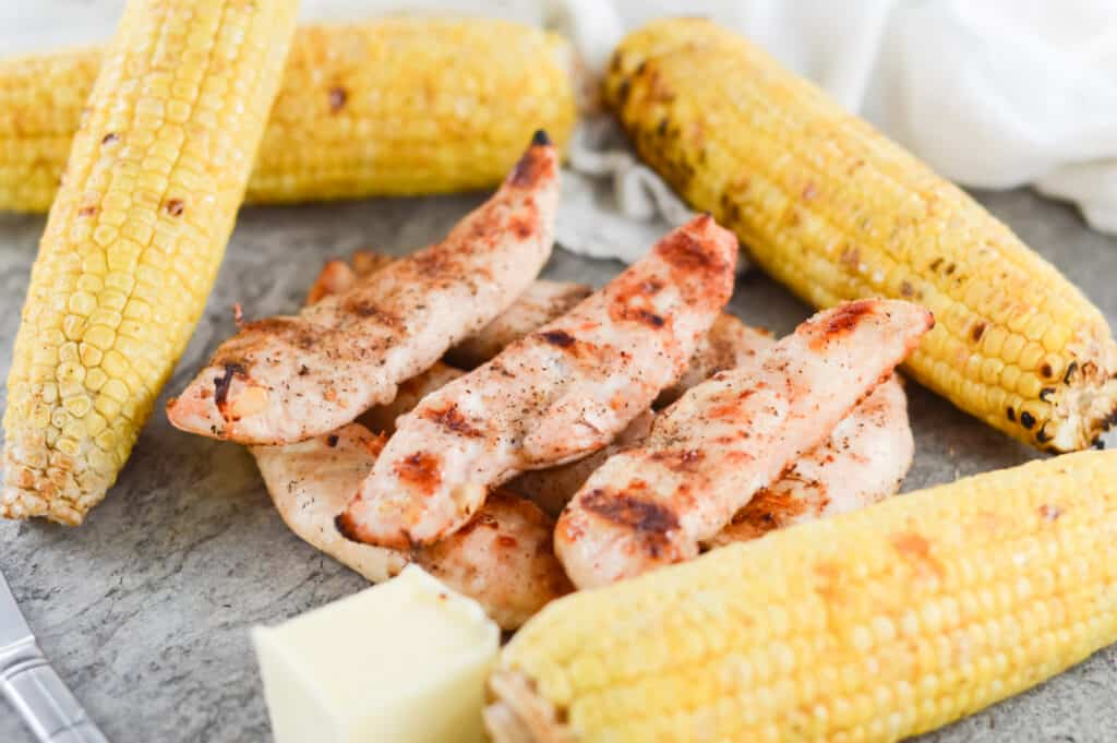 Grilled chicken surrounded by corn on the cob