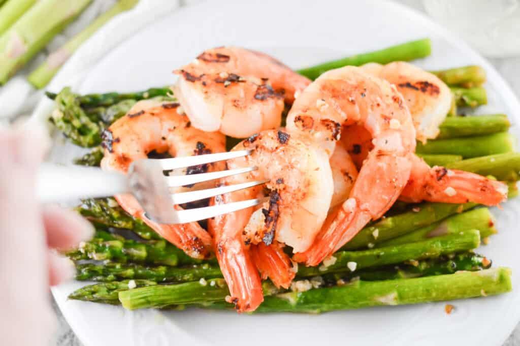Horizontal shot of fork picking up piece of blackened shrimp