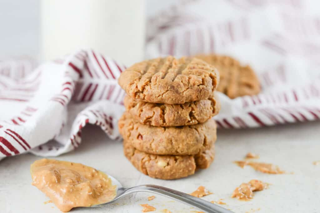 Horizontal shot of stacked cookies and spoon of peanut butter