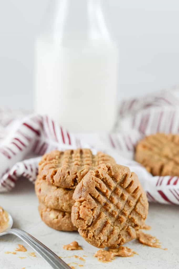 Vertical shot of three stacked peanut butter cookies behind one standing peanut butter cookie