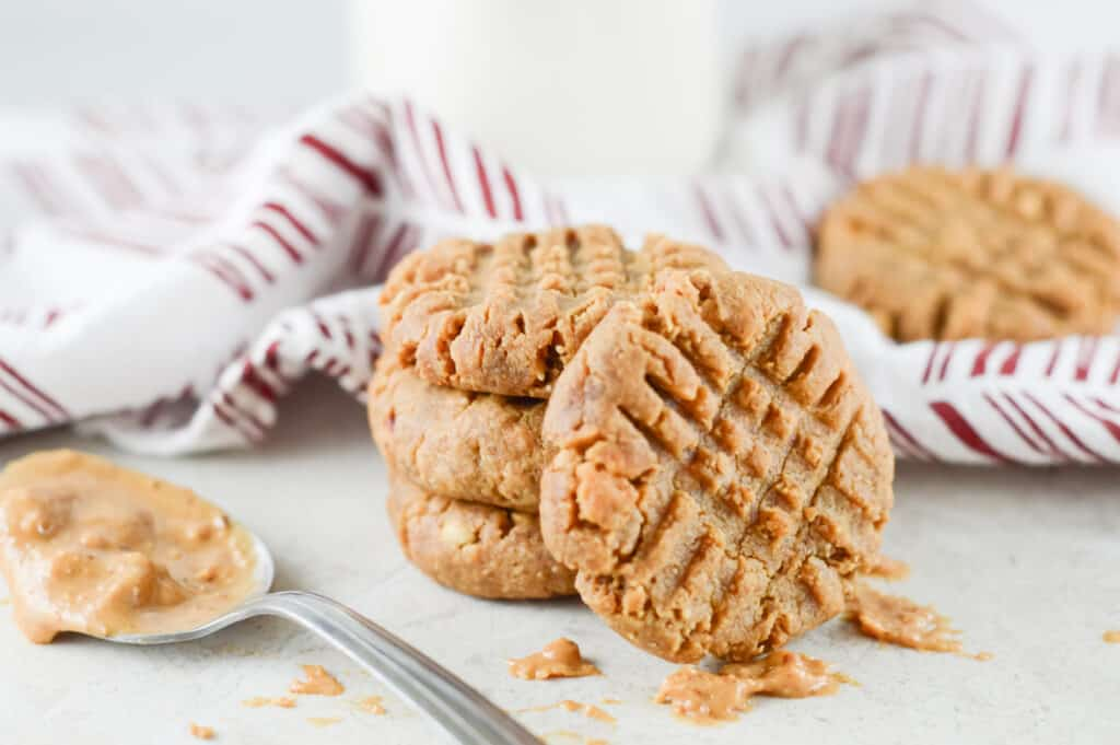 Horizontal close-up shot of stacked cookies with spoon and cloth in the background