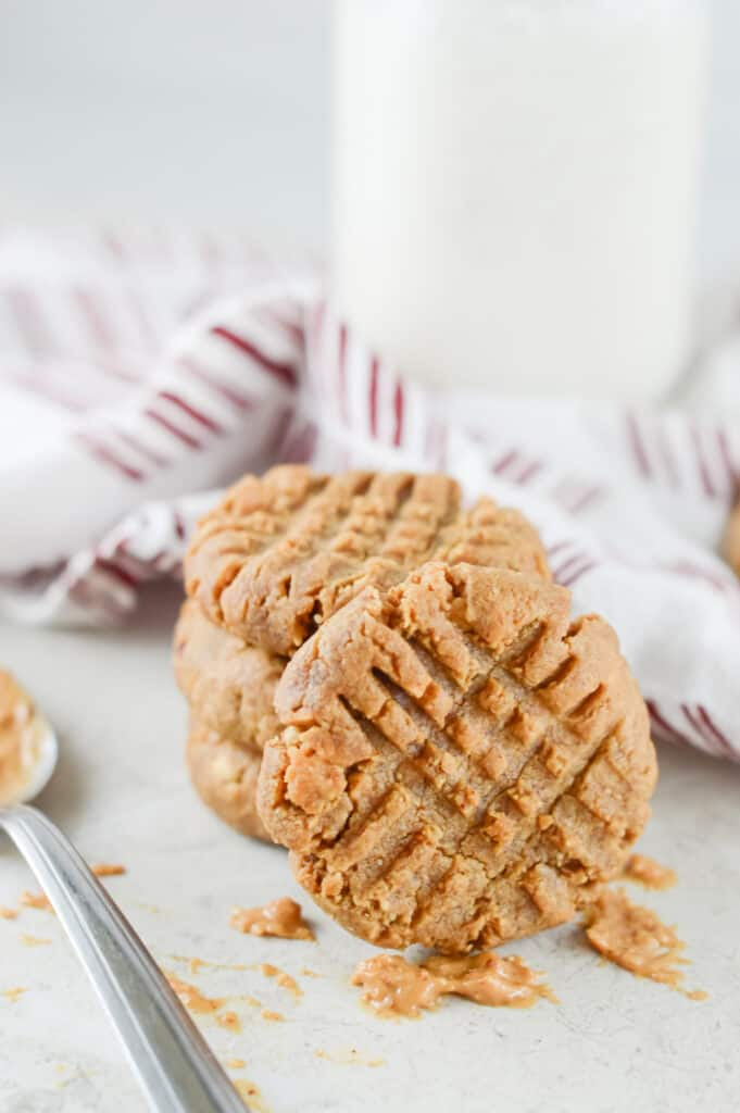 Vertical shot of cookies and spoon of peanut butter