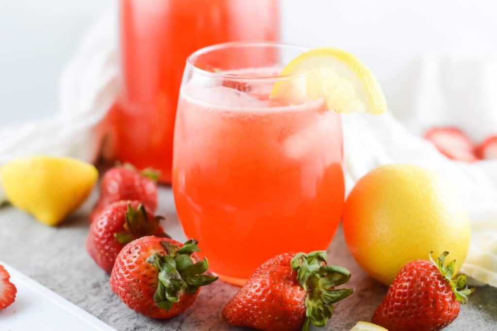 Horizontal shot of strawberry lemonade garnished with strawberries and lemons