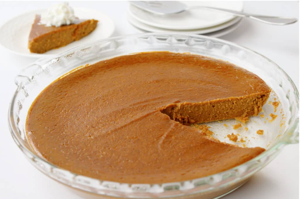 baking dish of pumpkin pie with one slice missing