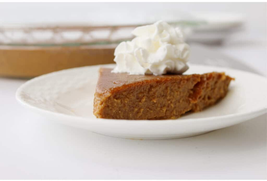 keto friendly pumpkin Pie with whipped cream on white plate